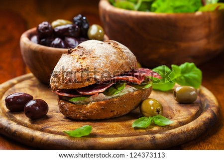 Sandwich with Italian salami, goat cheese and fresh olives - stock photo