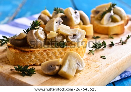 Sandwich with mushrooms and thyme on a wooden surface. - stock photo