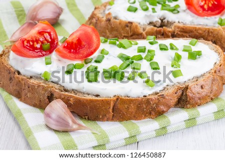 Sandwich with onion, cream cheese and tomatoes - stock photo