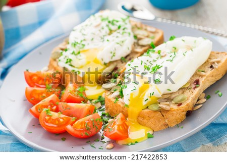Sandwich with poached egg and cherry tomatoes - stock photo