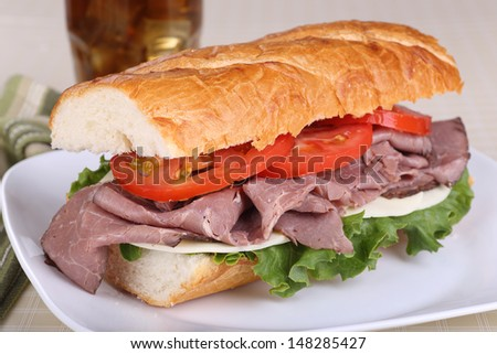 Sandwich with roast beef cheese lettuce and tomato on french bread on a plate - stock photo