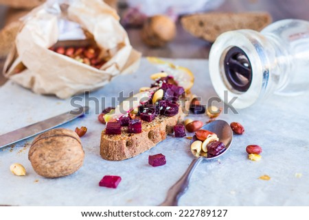 sandwich with roasted beets, nuts, pear and sesame on a wooden background - stock photo