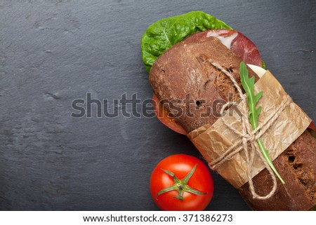 Sandwich with salad, ham, cheese and tomatoes on stone board. Top view with copy space  - stock photo