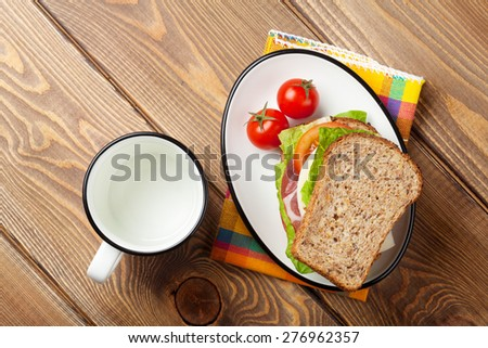 Sandwich with salad, ham, cheese and tomatoes on wooden table. Top view - stock photo