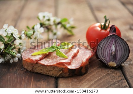 Sandwich with salami, red onion, tomato  and cherry flowers - stock photo