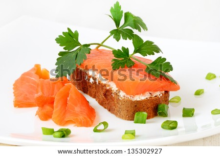 Sandwich with salmon and parsley on a white plate - stock photo