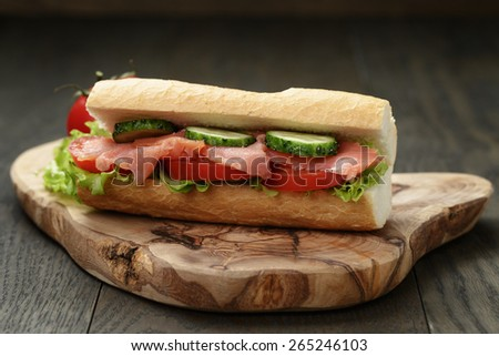 sandwich with salmon and vegetables on wood table - stock photo