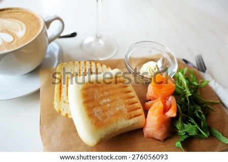 Sandwich with smoked salmon and salad with a cup of  coffee.  - stock photo