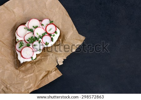Sandwich with sour cream, onions and radishes and dill on a package  on a isolated  black background - stock photo