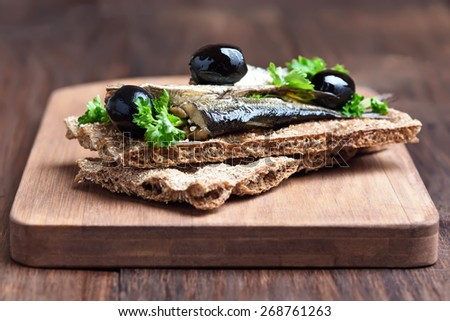 Sandwich with sprats and olives on crispbread over cutting board, close up view - stock photo