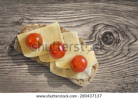 Sandwich with three fresh ripe juicy Tomatoes and Edam Cheese slices, placed on an old, wooden roughly treated, weathered, cracked Butcher Block surface. - stock photo