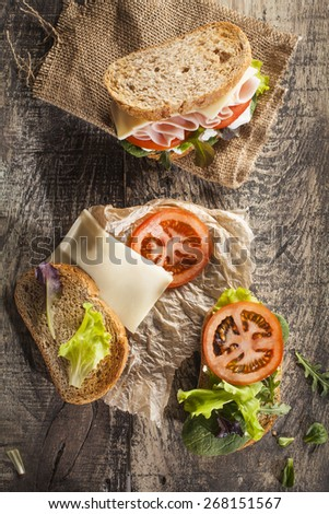 Sandwich with tomato, lettuce, ham and cheese - stock photo