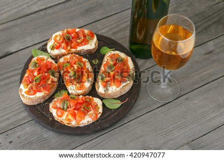 Sandwich with tomatoes, goat cheese and basil on a wooden table with a glass of white wine. Tasty appetizer wine - stock photo