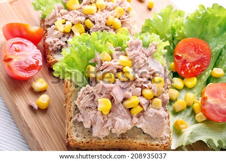 Sandwich with tuna and corn on wood background - stock photo