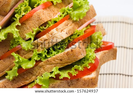 Sandwich with  vegetables and bacon on bamboo close up - stock photo