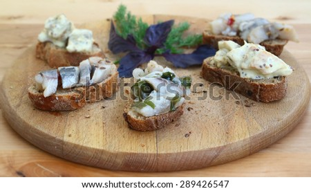 Sandwiches of rye bread and herring. Pieces of fish are herring on bread. Sandwiches with byboy on a wooden boards background. Traditional food for the reception. Fish dishes. Scandinavian cuisine. - stock photo