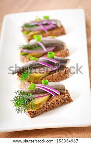 Sandwiches of rye bread with herring, onions and herbs. - stock photo