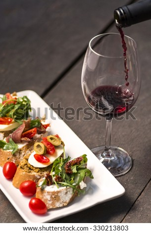 Sandwiches on a plate and wine splash - stock photo