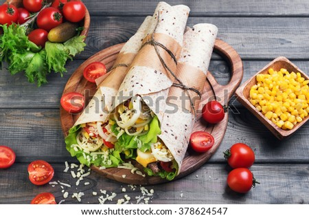 Sandwiches twisted roll Tortilla three pieces on a wooden cutting board on a gray background, lettuce, cucumbers malosollnye, cherry tomatoes, corn, onion rings, meat - stock photo