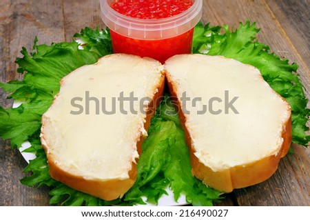 sandwiches with butter on a plate and a bank with salmon caviar on a wooden table - stock photo