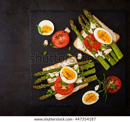 Sandwiches with caramelized asparagus, feta cheese, tomatoes and eggs. Top view - stock photo