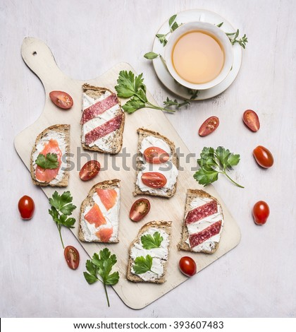 sandwiches with cheese, herbs and red fish, lunch with green tea with thyme on wooden rustic background top view close up - stock photo