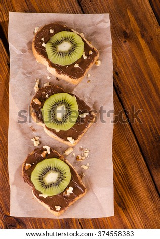 Sandwiches with chocolate paste, kiwifruit and walnuts on a wooden background, top view - stock photo