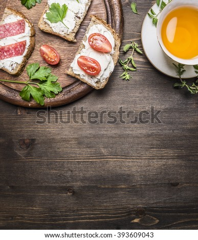 sandwiches with curd cheese with parsley, cherry tomatoes and salmon on a cutting board and a cup of tea with thyme  border ,place for text - stock photo