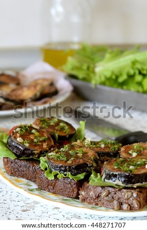 Sandwiches with fried eggplant, fresh tomato, lettuce, dill and garlic on a dish. Lettuce, olive oil, knife on the kitchen table. Fried eggplant on a plate  - stock photo