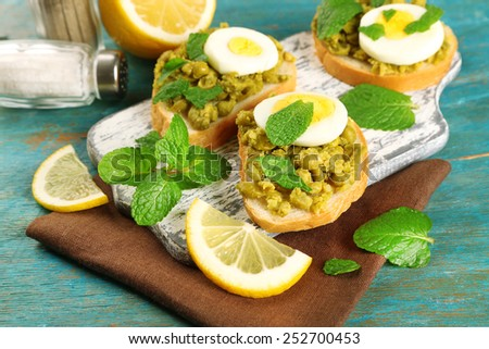 Sandwiches with green peas paste and boiled egg on cutting board with napkin on color wooden background - stock photo