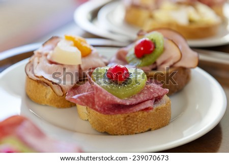 Sandwiches with ham, salami, orange and kiwi on a plate - stock photo