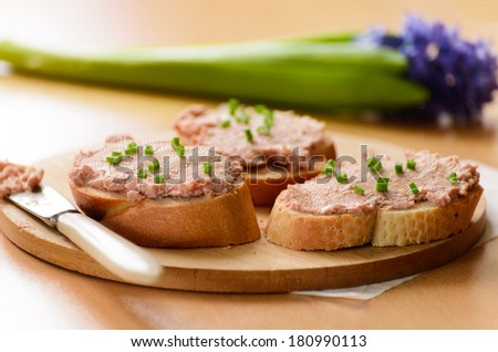 Sandwiches with meat pate. Decorated with green onion rings. - stock photo