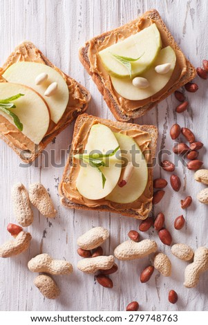sandwiches with peanut butter and an apple on the table close-up. vertical top view  - stock photo