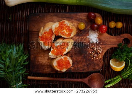 Sandwiches with red caviar, good wholesome breakfast for the entire family, in white crispy baguette buttered salted red caviar on top, served with all the cherry tomatoes - stock photo