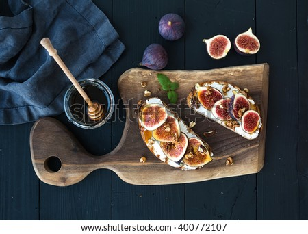 Sandwiches with ricotta, fresh figs, walnuts and honey on rustic wooden board over black backdrop, top view - stock photo