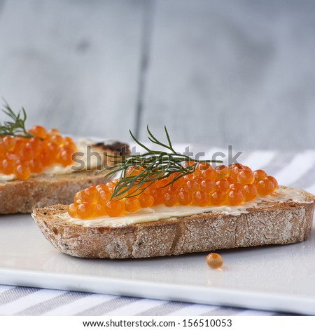 Sandwiches with salmon red caviar on a wooden background - stock photo