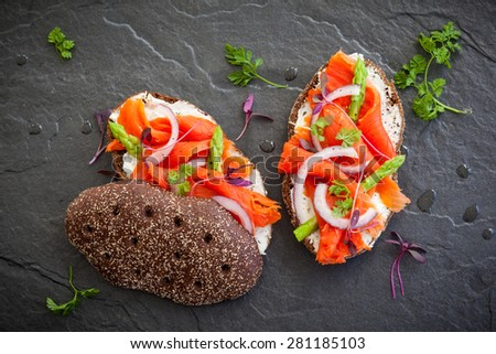 Sandwiches with smoked salmon and asparagus on the black stone background, top view - stock photo