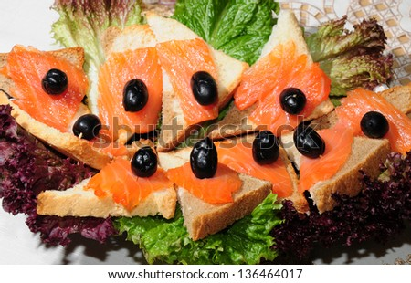 Sandwiches with smoked salmon on lettuce leaves - stock photo