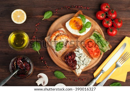 Sandwiches with various useful and tasty fillings such as ham, egg, cheese, dried tomatoes and fresh vegetables. The concept of useful and tasty breakfast. - stock photo