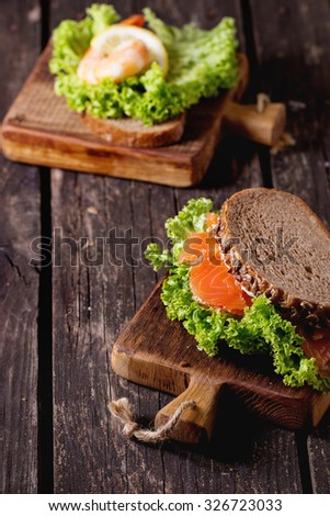 Sandwiches with whole wheat bread, fresh salad, shrimp and salted salmon on little wooden cutting board over old wooden table. Rustic style. - stock photo