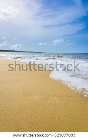sandy beach and calm blue sea surf - stock photo
