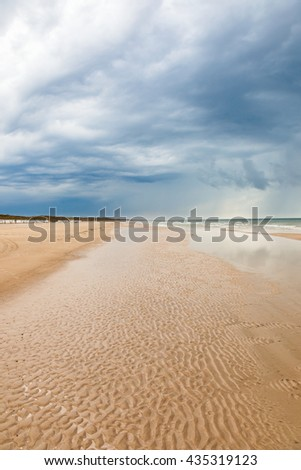 Sandy beach at the sea and storm clouds in the sky - stock photo