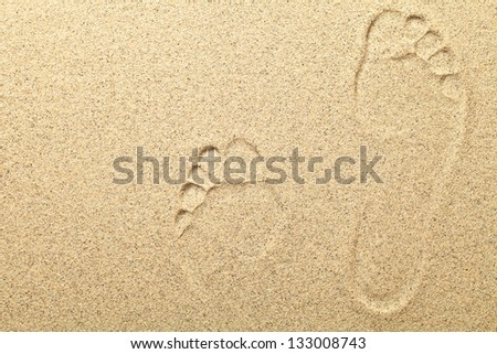 Sandy beach background with footprints. Copy space, macro shot - stock photo