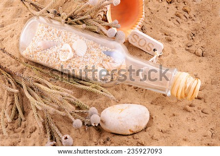 sandy beach concept with letter in bottle - stock photo