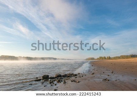 Sandy beach misty river early in the morning - stock photo