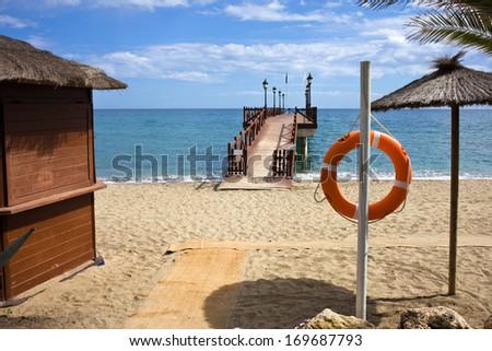 Sandy beach scenery by the Mediterranean Sea in Marbella, Andalusia region, Costa del Sol, Spain - stock photo