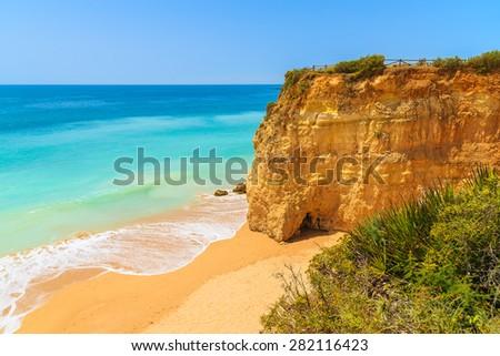 Sandy beach with cliff rocks on beautiful Praia da Rocha beach, Algarve region, Portugal - stock photo
