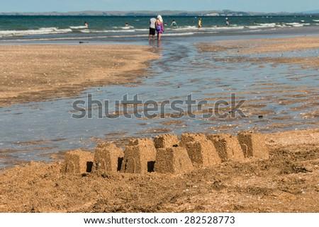 sandy beach with sandcastles - stock photo