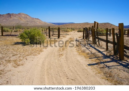 Sandy dirt road runs into abandoned wooden corral in the Mojave desert in California. - stock photo