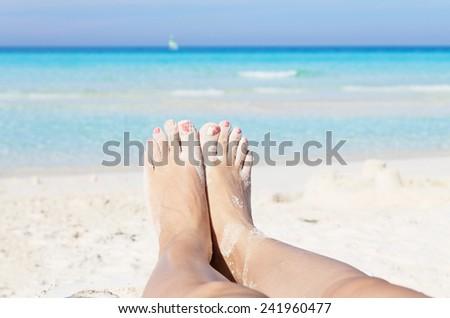 Sandy feet on the beach - stock photo